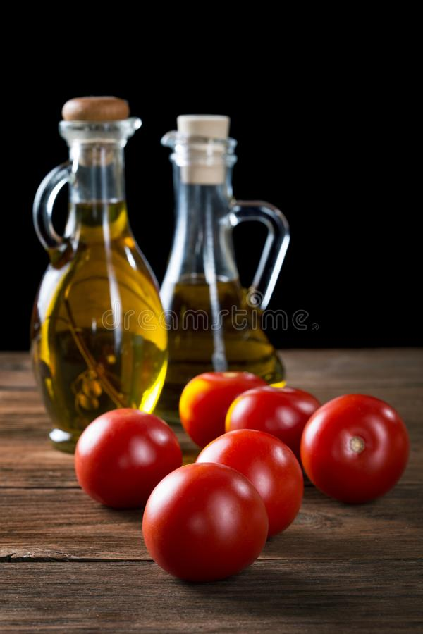 Tomatoes and bottles of olive oil stock photo