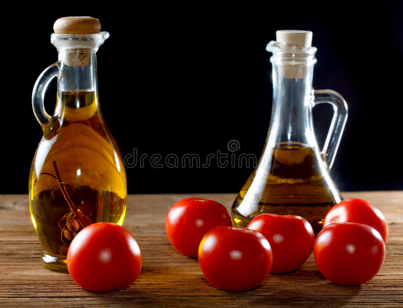 Tomatoes and bottles of olive oil on table stock image