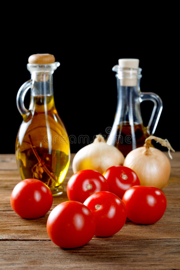 Tomatoes and bottles of olive oil on table stock photos
