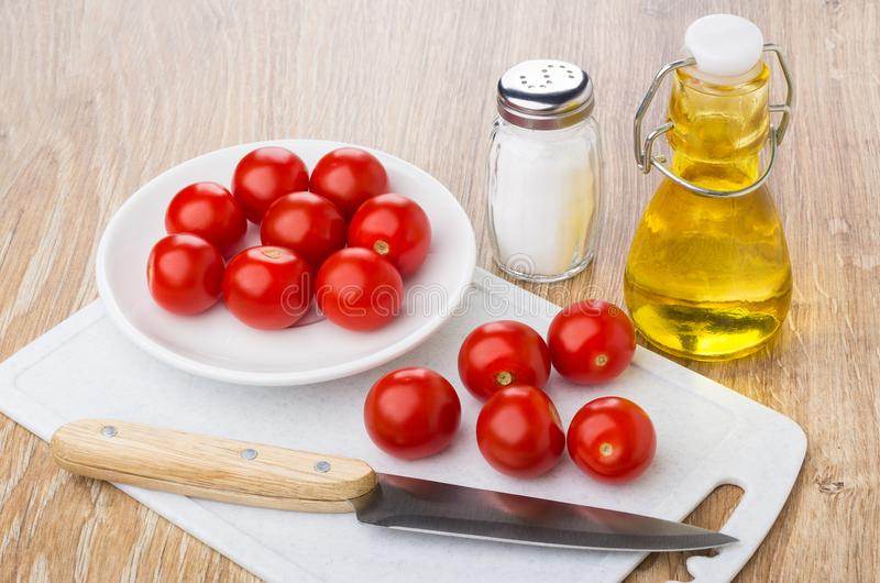 Tomatoes cherry in saucer, on cutting board, vegetable oil, knife royalty free stock image