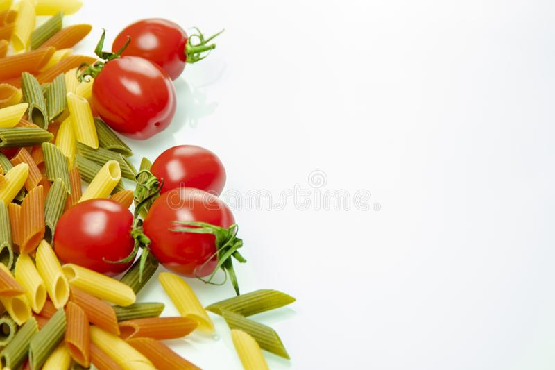 Tomatoes and colored pasta spread on the right stock photography