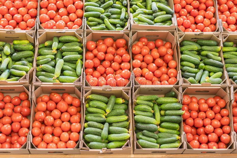 Tomatoes and cucumbers in boxes in the store. Beautiful background of vegetables. Healthy eating. Food for Vegetarians. Healthy li stock photos