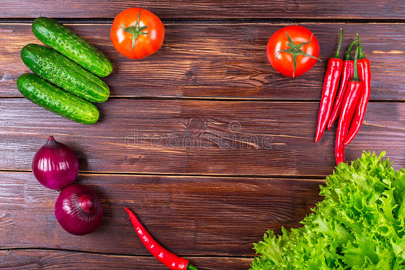 Tomatoes, cucumbers, onions, greens. Vegetables on an old table: tomatoes, cucumbers, pepper, onions, lettuce leaves royalty free stock image