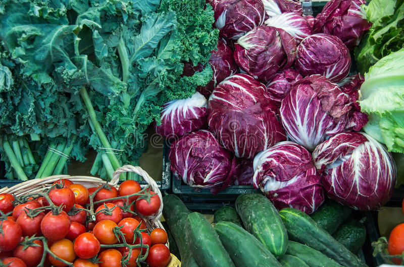 Tomatoes; cucumbers; salad; lettuce; radicchio;. Vegetable stand at a market stock photos