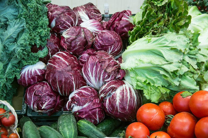 Tomatoes; cucumbers; salad; lettuce; radicchio;. Vegetable stand in a market royalty free stock image