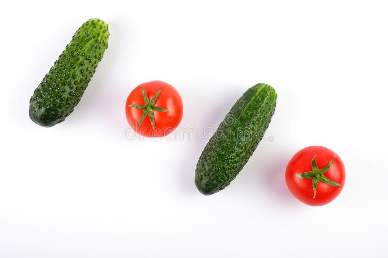 Tomatoes and cucumbers on white background diagonally royalty free stock photo