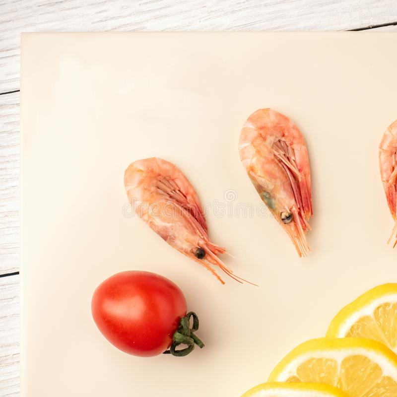 Tomatoes and curves on a kitchen cutting board made of artificial stone.  stock photos