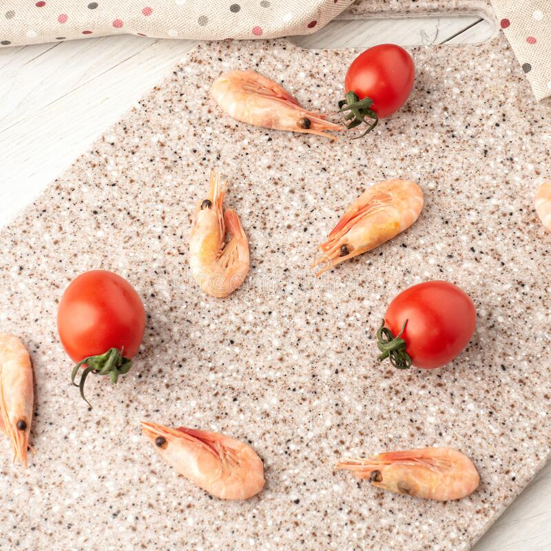 Tomatoes and curves on a kitchen cutting board made of artificial stone.  royalty free stock images