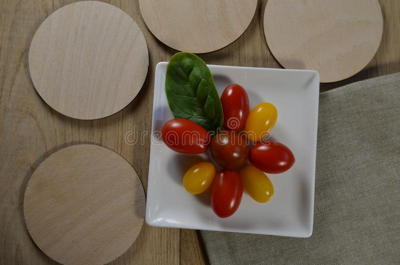 Tomatoes of different colors on a saucer royalty free stock photos