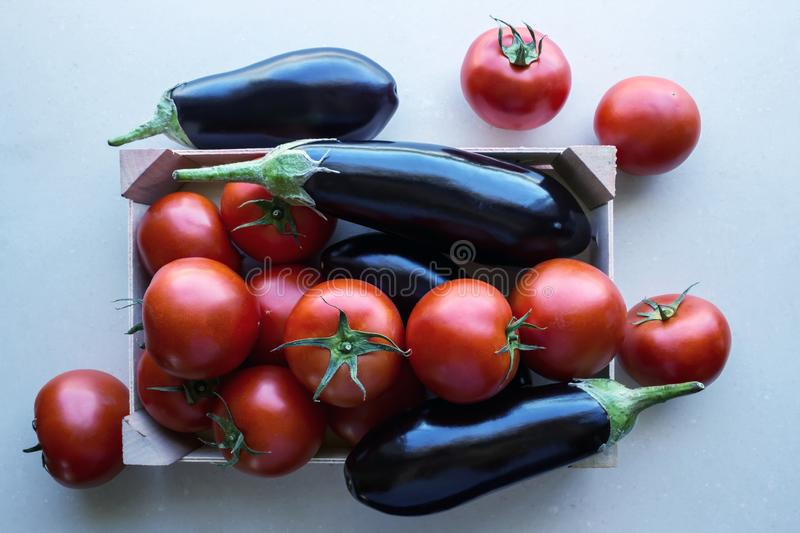 Tomatoes and eggplants  in a wooden crate. stock image
