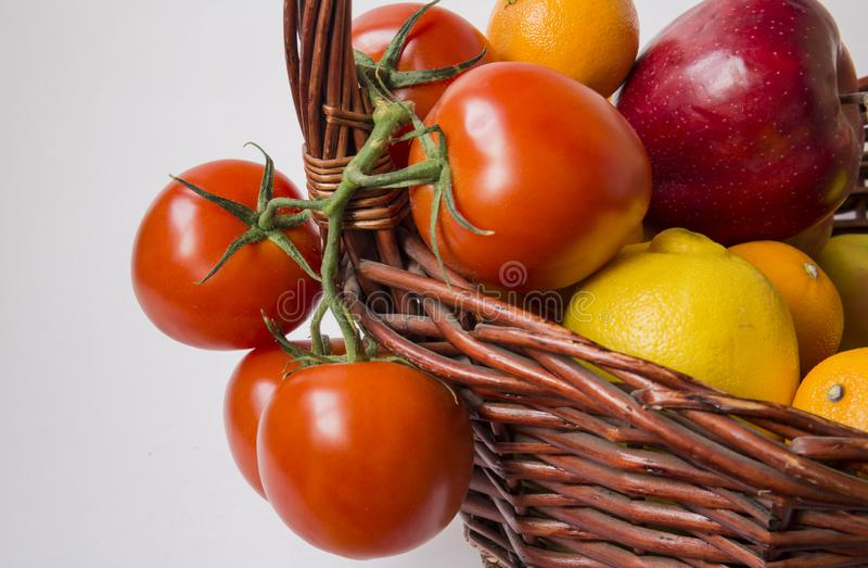 Tomatoes and fruits in a basket. stock images