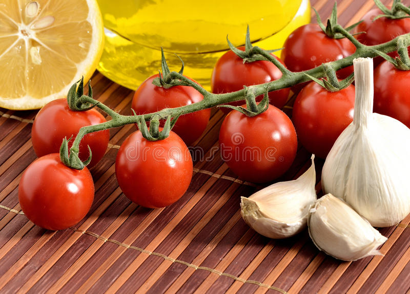 Tomatoes, garlic, lemon, tomatoes and oil. Mediterranean foods concept. lemon, garlic, tomatoes and oil stock photo