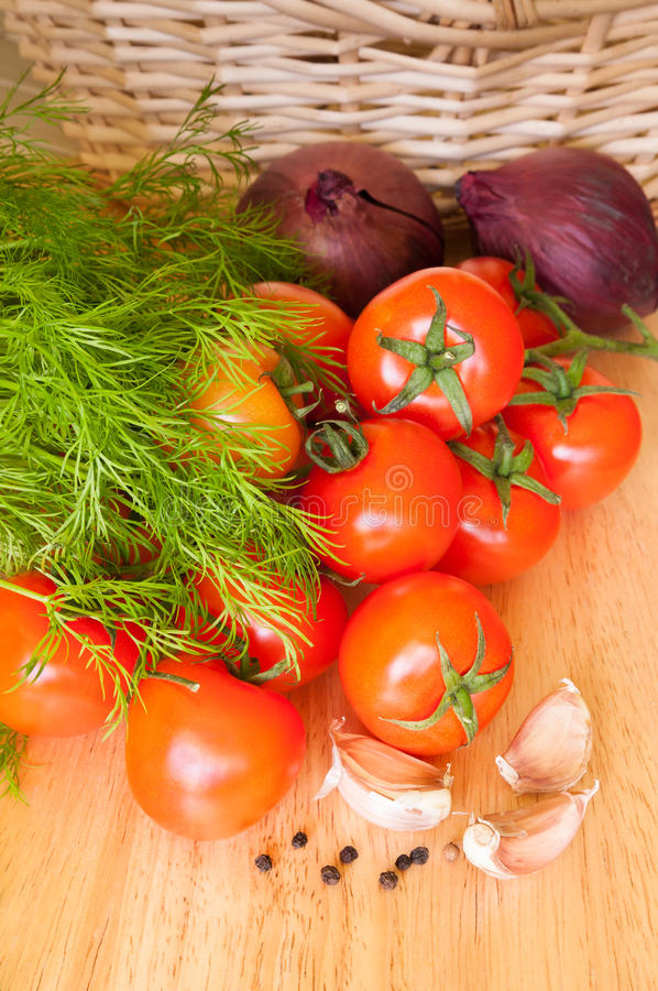 Tomatoes garlic onions and herbs on the table. Tomatoes, garlic, onions and herbs on the table royalty free stock photo