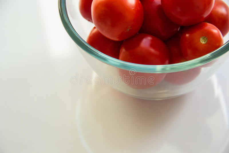 Tomatoes in a glass bowl stock photos