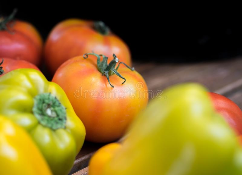 Tomatoes and green-yellow bell peppers. On wooden board. Selective focus stock photography