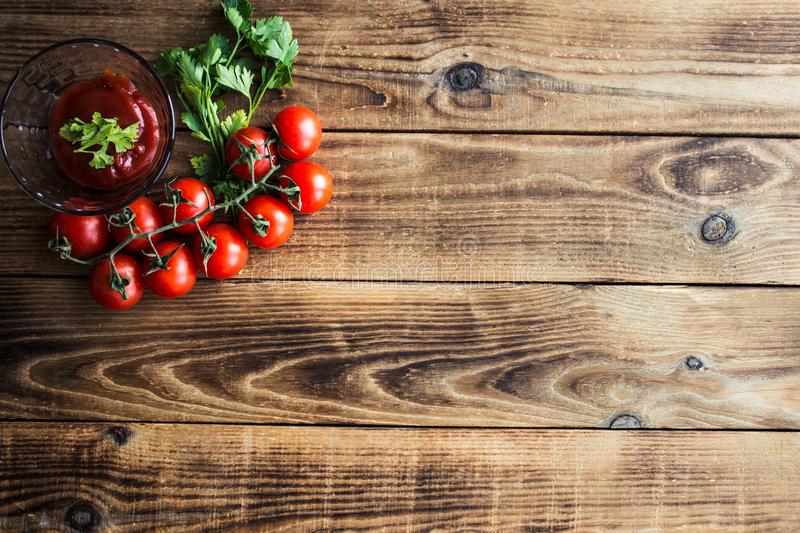 Tomatoes with greens and sauce on wooden background stock photos