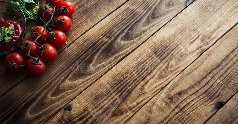 Tomatoes with greens and sauce on wooden background stock photography