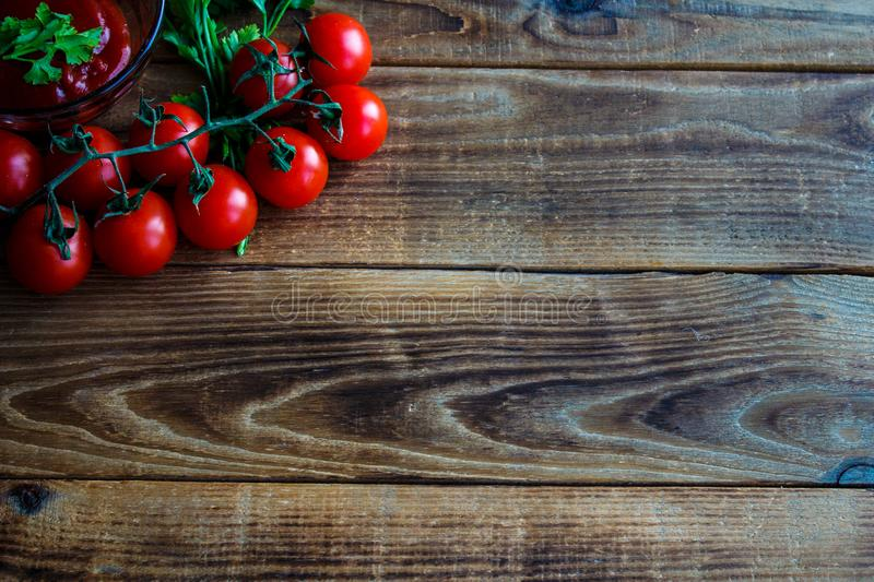 Tomatoes with greens and sauce on wooden background royalty free stock image
