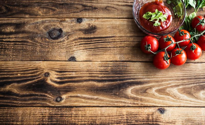 Tomatoes with greens and sauce on wooden background royalty free stock photography