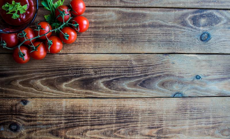 Tomatoes with greens and sauce on wooden background royalty free stock photo
