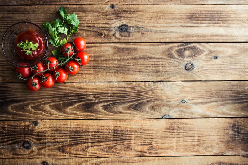 Tomatoes with greens and sauce on wooden background stock image