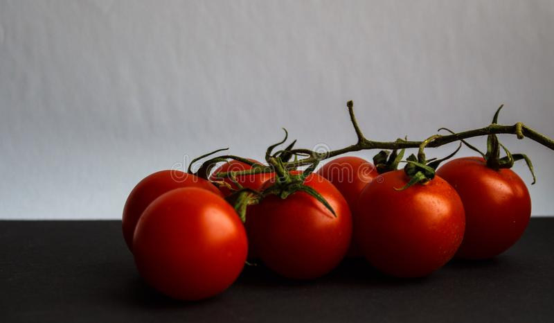 Tomatoes with greens on white background stock photos
