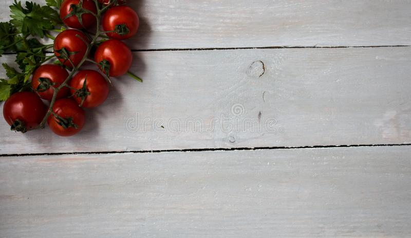 Tomatoes with greens on wooden background stock images