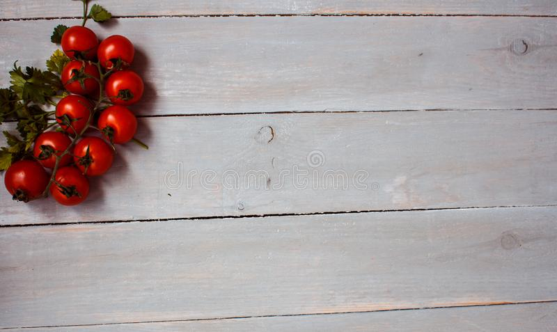 Tomatoes with greens on wooden background stock photos