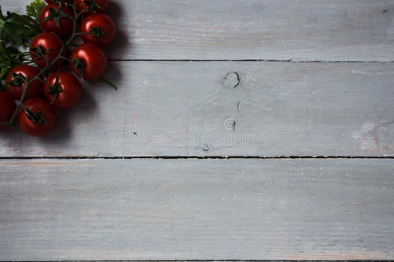 Tomatoes with greens on wooden background stock photo
