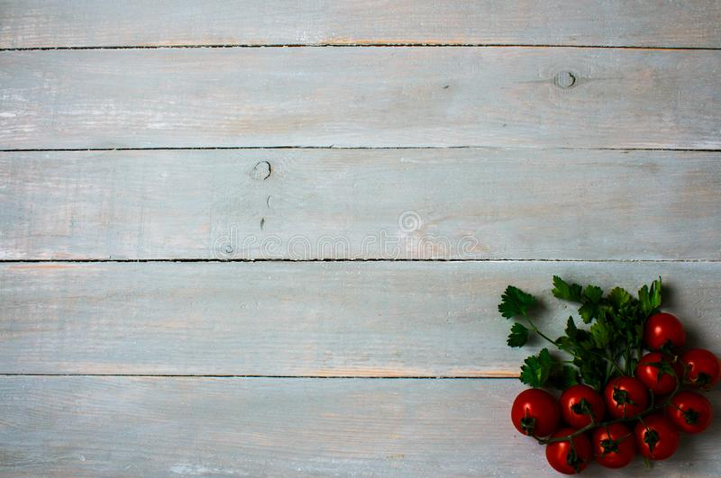 Tomatoes with greens on wooden background royalty free stock photography