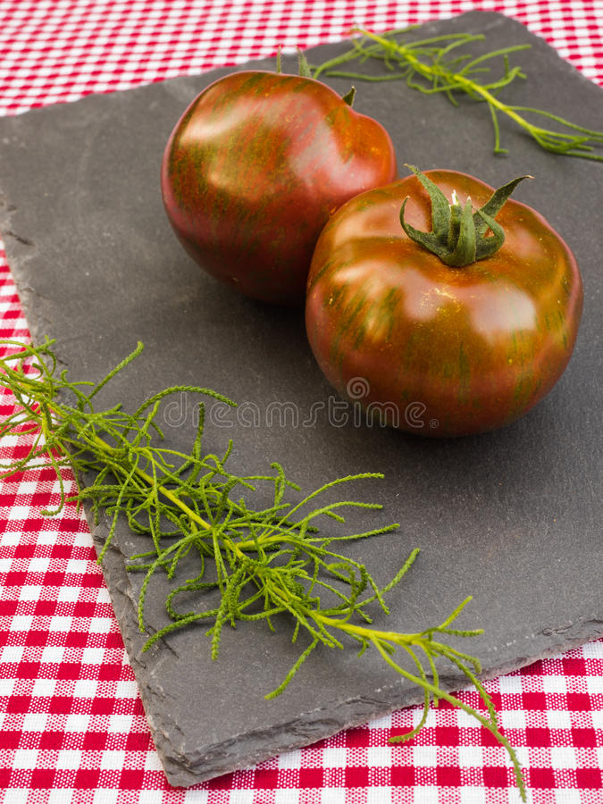 Tomatoes and herbs on a slate stock images