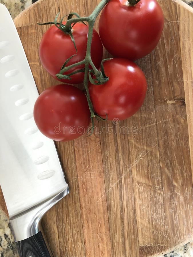 Tomatoes with knife. A chefs knife on a wooden cutting board with a vine of tomatoes royalty free stock image