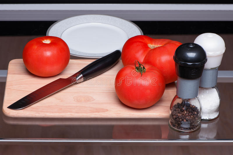 Tomatoes and knife on a chopping board. Tomatoes are sliced and salted also by pepper stock photos
