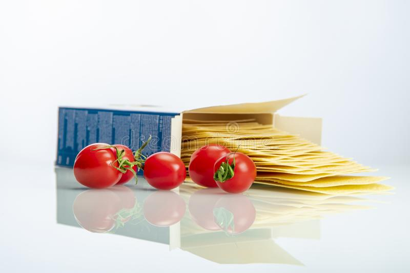 Tomatoes with lasagna on white reflexive glass stock photo