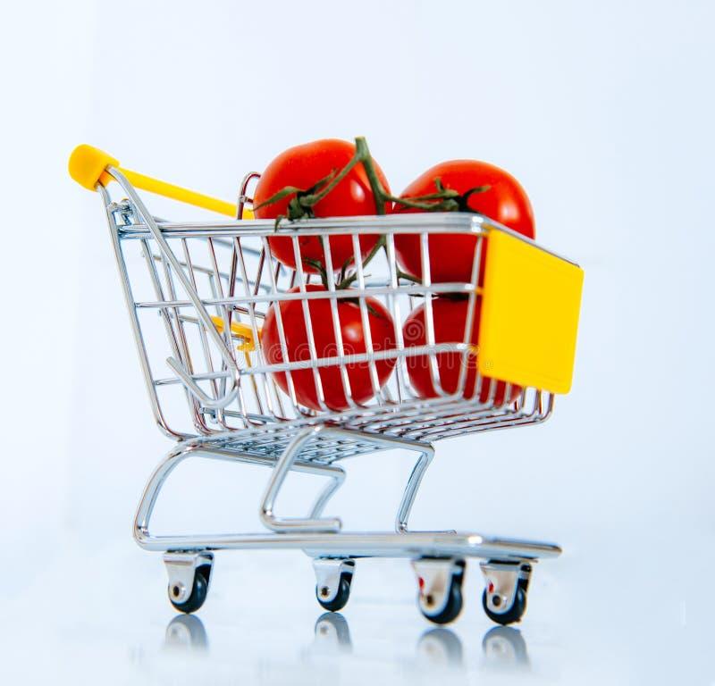 Tomatoes in mini supermarket cart royalty free stock photos