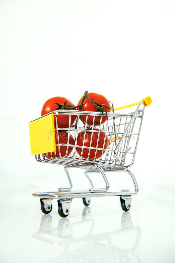Tomatoes in mini supermarket cart royalty free stock photography