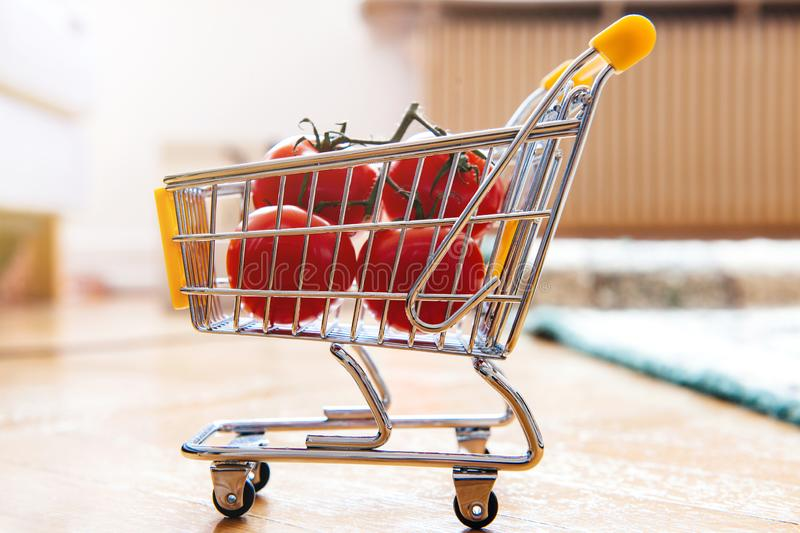 Tomatoes in mini supermarket cart royalty free stock images