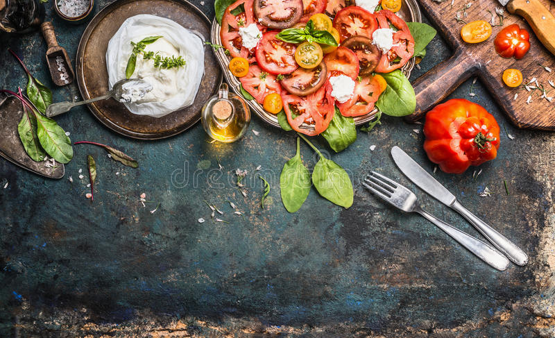 Tomatoes and mozzarella salad, preparation on dark aged rustic background, top view. Italian lunch royalty free stock image