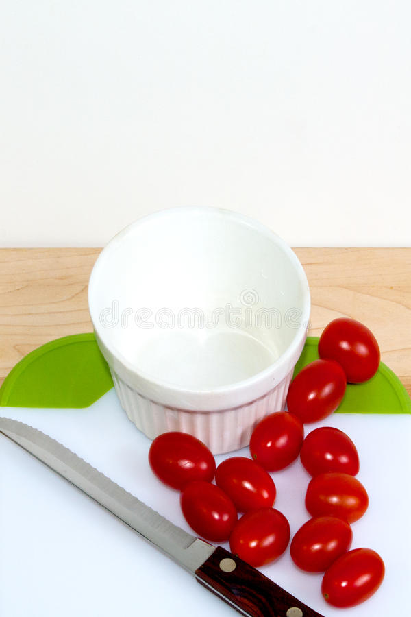 Tomatoes none cut. Grape tomatoes on a cuttting board with a white bowel - none cut stock photo