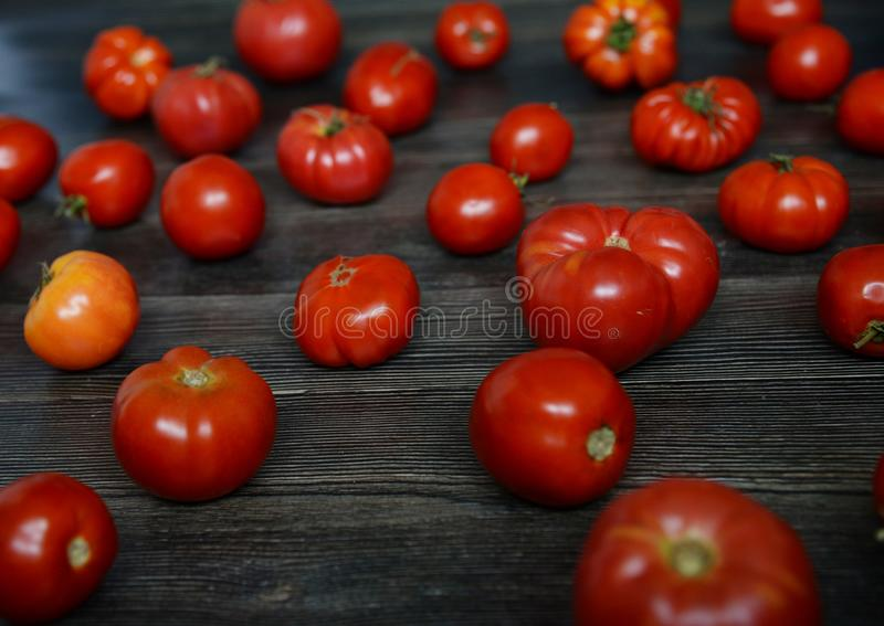 Tomatoes on the old table. Red Food background. Tomatoes pattern. Top view of fresh vegetable on a dark wooden royalty free stock photo