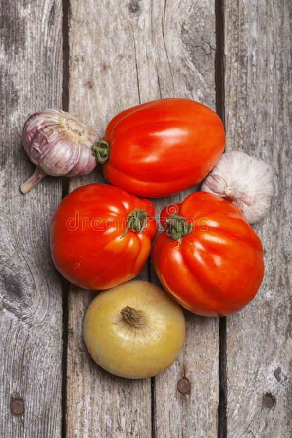 Tomatoes, onion and garlic on the table. Tomatoes, onion and garlic on the vintage wooden table royalty free stock photos