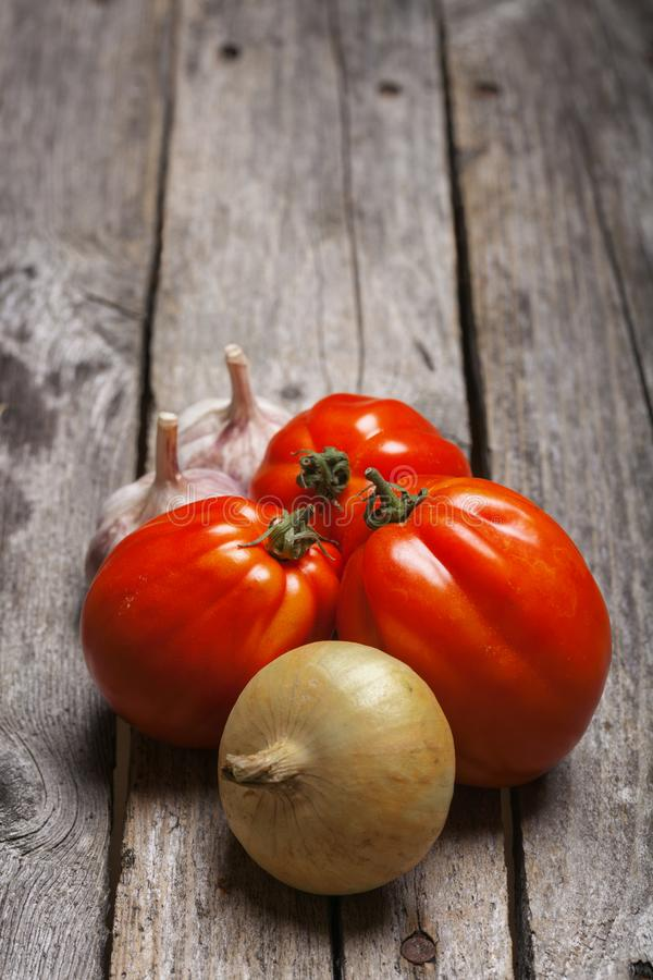 Tomatoes, onion and garlic on the table stock photography