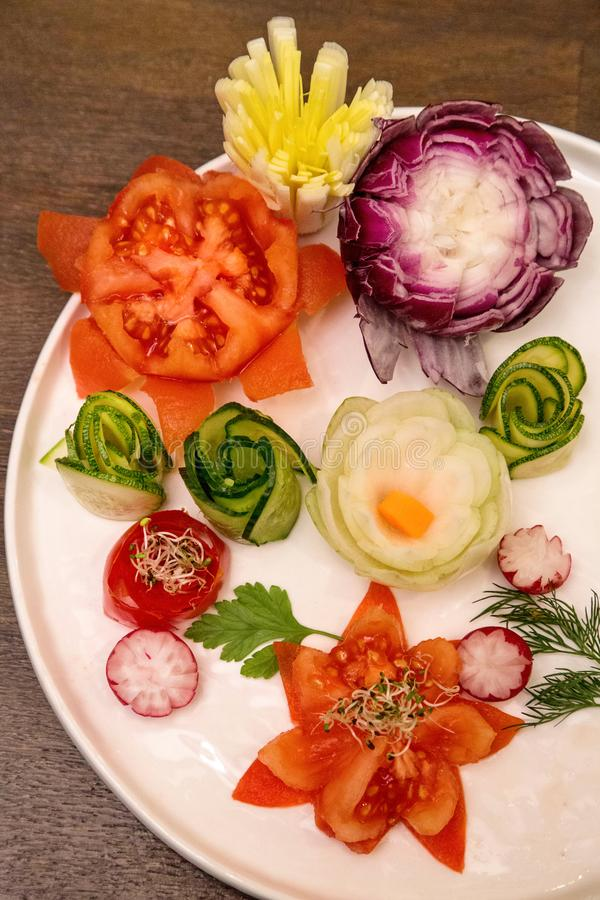 Carving Flowers from Vegetables. Tomatoes, onions, bell peppers, leeks, cucumbers and radishes turned into decorative flowers to decorate apricot plates or stock image