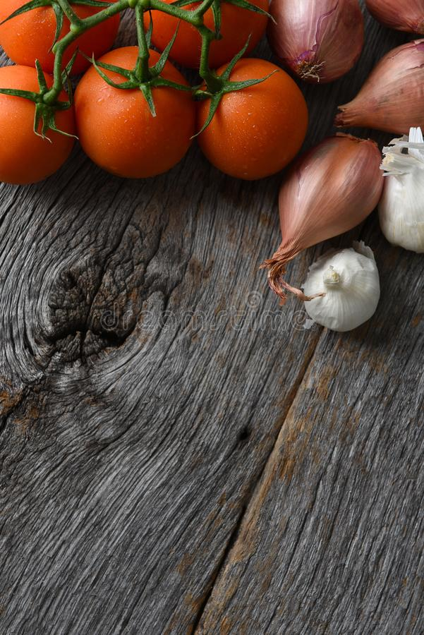 Tomatoes, onions and garlic on a rustic wood kitchen table stock photography