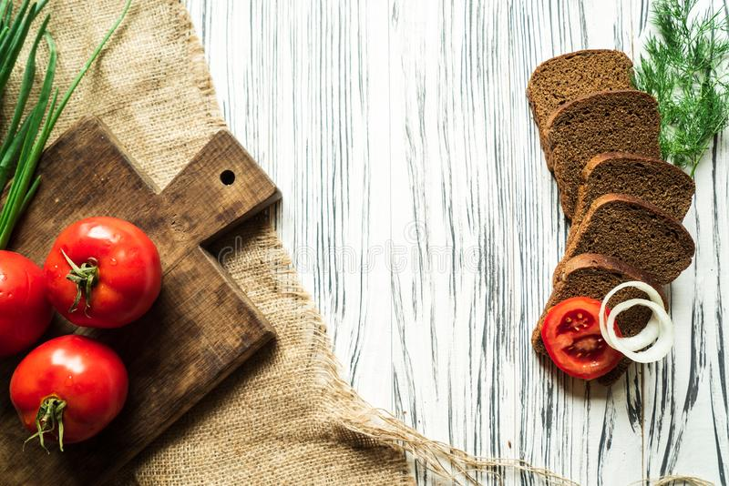Tomatoes and onions, greens and rye bread on a white wooden table royalty free stock photography