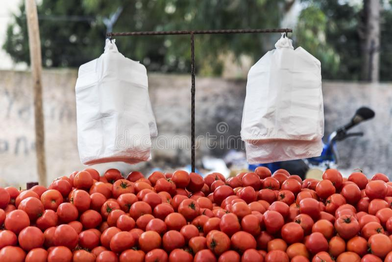 Tomatoes on a outdoor market stall, outdoor, healthy fruits for people with white plastic bags for shopping. No returnable plastic for environment stock photos