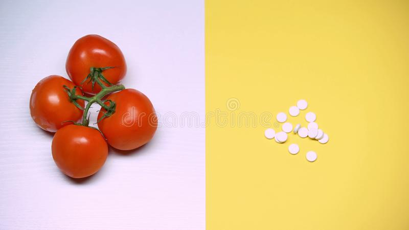 Tomatoes and pills macro shot, diet and health, genetically modified products royalty free stock photo