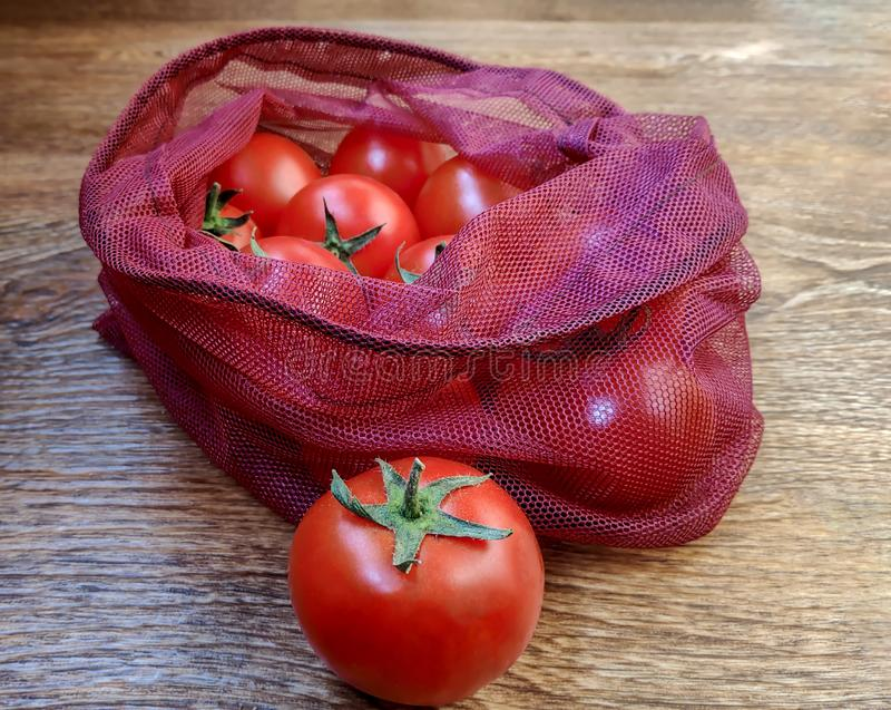 Tomatoes in reusable eco bags for fruits and vegetables royalty free stock image
