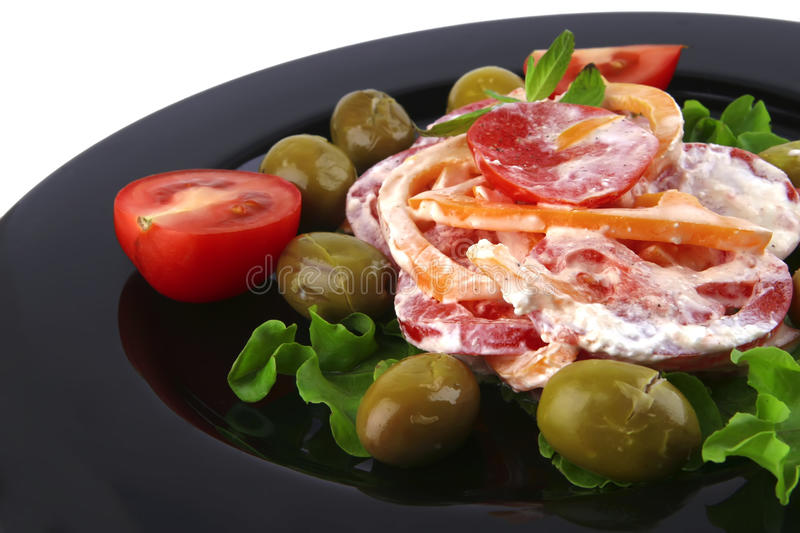 Tomatoes salad and olives. On black dish royalty free stock images