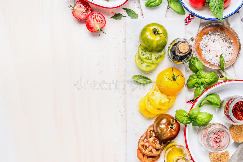 Tomatoes salad preparation. Tomatoes cooking ingredients on white marble cutting board. Various Colorful sliced tomatoes on white. Wooden background, top view royalty free stock photography